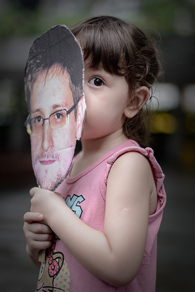 A child holds a cut out of Edward Snowden during the protest in Hong Kong